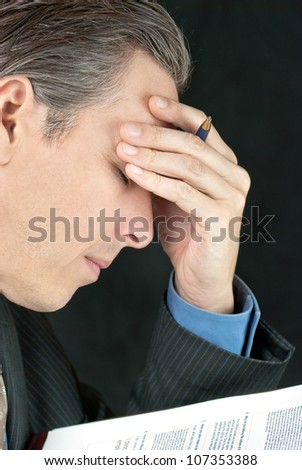 Close-up of a stressed businessman adjusting his tie.