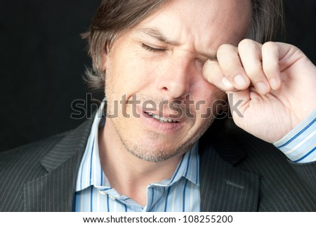 Close-up of a stressed businessman rubbing his eyes. - stock photo