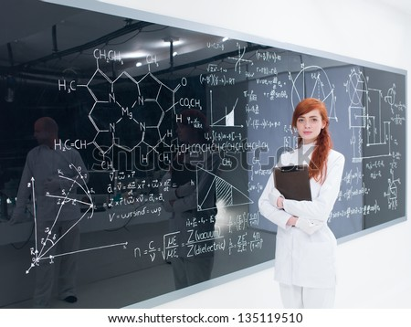 close-up of a student in a chemistry lab satisfied  looking in the camera while holding in hands a clip-board  and with  blackboard with formulas on the background - stock photo