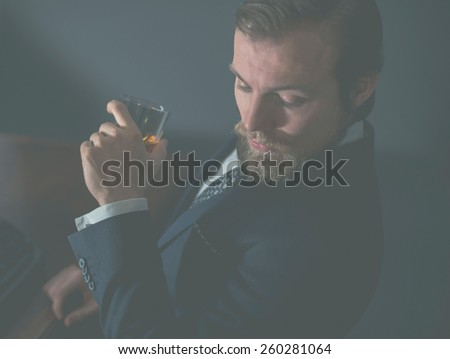 Close up of a stylish handsome bearded man enjoying a brandy or whiskey while looking thoughtfully downwards, aged effect - stock photo