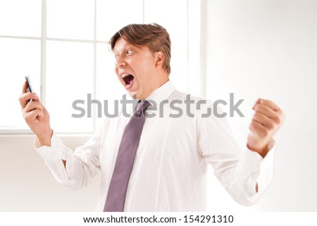 Close up of a successful and laughing businessman on the phone in his office
