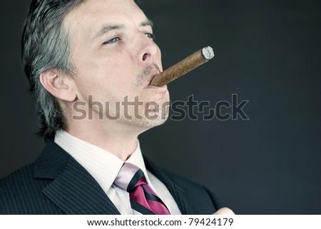 Close-up of a successful businessman enjoying a cigar. - stock photo