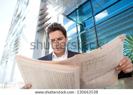 Close up of a successful businessman standing by a modern office building reading the stock shares pages of a financial newspaper, outdoors. - stock photo