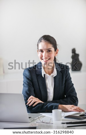 Close-up of a successful middle age businesswoman with dark hair sitting at her white desk in her office. She is wearing a black suit jacket, holding her chin, her laptop next to her