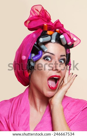 Close-up of a surprised young woman with hair curlers