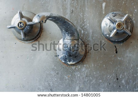 close up of a tap set set in a stainless steel sink or trough. Colourfully grungy and disgusting. Actually shot in an art classroom - stock photo