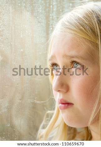 close-up of a teen or child looking out a rainy window