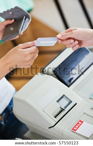 Close-up of a teen woman paying with her credit card in a shop - stock photo