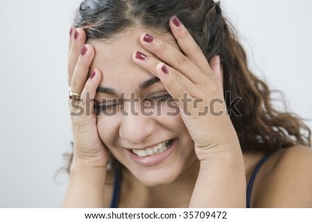 Close-up of a teenage girl laughing with her head in her hands