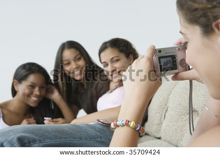 Close-up of a teenage girl taking a picture of her friends with a digital camera