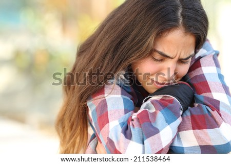 Close up of a teenager girl worried and sad crying outdoors               - stock photo