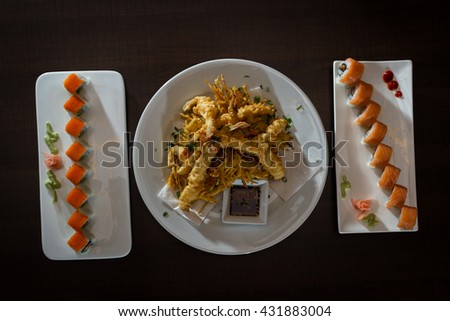 close up of a tempura shrimp surrounded by two fresh sushi rolls served on white plates on a wooden table - stock photo