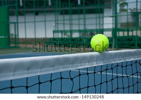 Close-up of a tennis ball touching the net tape  - stock photo