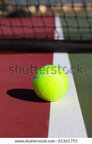 Close-up of a tennis ball with the net in the background. - stock photo