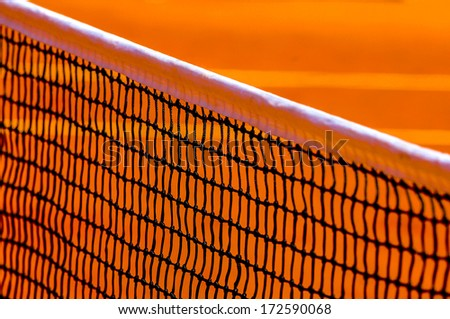 Close up of a tennis net with the red ground on background - stock photo
