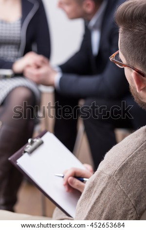 Close-up of a therapist holding a flipboard during a session with a couple in the blurred background - stock photo