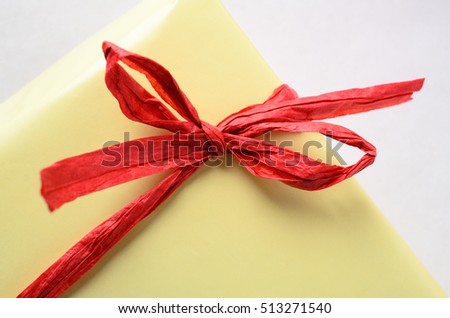 Close up of a tied red raffia bow around a yellow gift wrapped package.