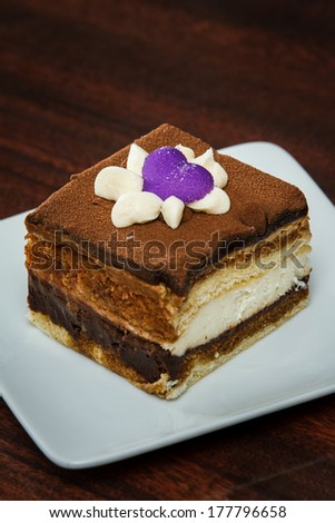 close up of a tiramisu slice garnished with a purple hart on top served on a white plate