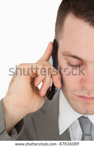 Close up of a tired businessman making a phone call against a white background