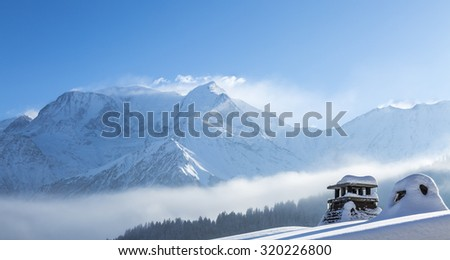 Close-up of a top of a chalet in front of a beautiful Mont Blanc winter landscape  - stock photo