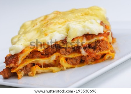 Close-up of a traditional lasagna made with minced beef bolognese sauce topped with basil leafs served on a white plate - stock photo