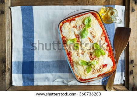 Close-up of a traditional lasagna made with minced beef bolognese sauce topped with basil leafs. copy space - stock photo
