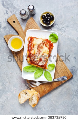 Close-up of a traditional lasagna made with sauce bolognese sauce topped with basil leaves - stock photo