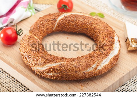 Close up of a traditional Turkish bagel (simit) with cream cheese, tomato and tea - stock photo