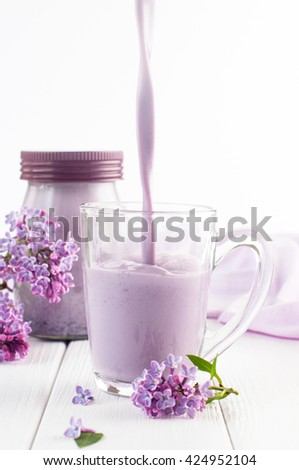 Close up of a transparent glass cup with pouring bilberry milkshake near lilac flowers on the white wooden background. Selective focus and small depth of field. - stock photo