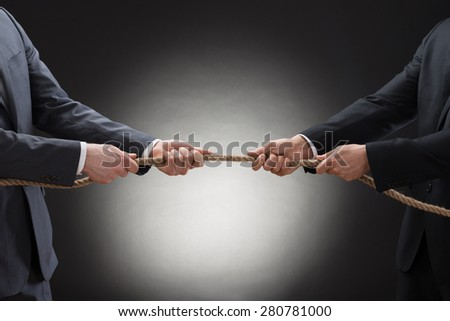 Close-up Of A Two Businessman Pulling Rope In Opposite Direction - stock photo