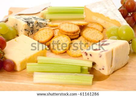 Close up of a variety of cheese and garnishes on a wooden cheeseboard