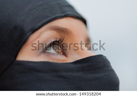 Close up of a veiled young woman/Veiled looking up - stock photo