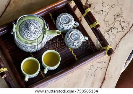 Close up of a Vietnamese teapot set with cups on a bamboo tray