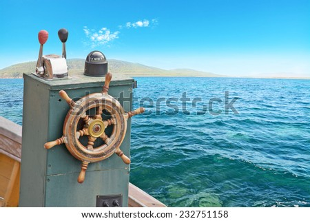 close up of a vintage boat wheel on the water. Shot in Sardinia, Italy - stock photo