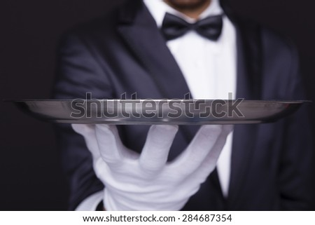Close-up of a waiter holding an empty silver tray against dark background - stock photo