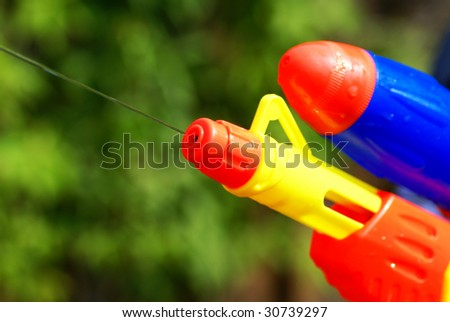 Close up of a water pistol in front of green bushes.