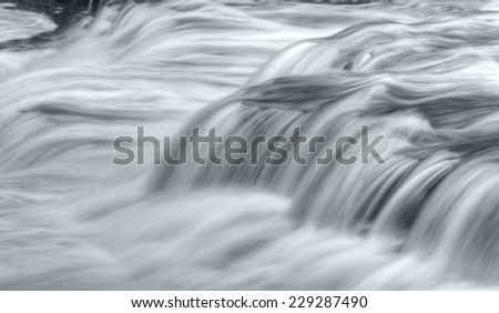 Close up of a waterfall during high water flow. Taken with a slow shutter speed to smooth out the flow of the water as is rushes by. - stock photo