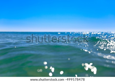 Close up of a wave in the sea with sun light reflections against a deep blue sky