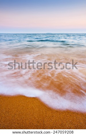 Close up of a wave washing up on the shore. - stock photo
