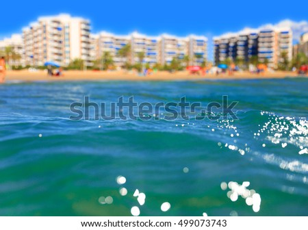 Close up of a wave with a holiday seaside resort in the background against as deep blue sky in Europe