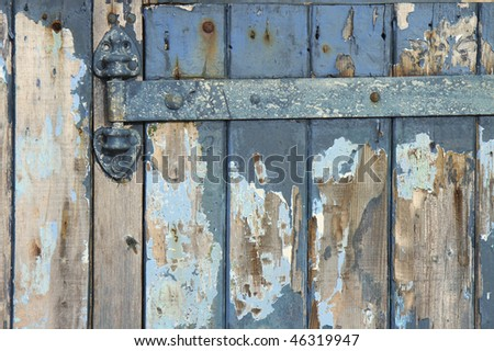Close up of a weathered blue wooden door and hinge on a beach hut in Hayling Island near Portsmouth, England - stock photo