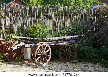 close-up of a wheel on an old wooden cart with rusty parts in the sunlight in the summer