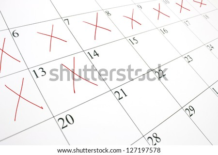 close up of a white calendar page with some of the days crossed off with a red X - stock photo