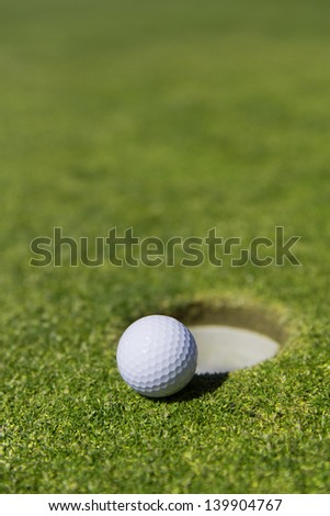 close up of a white golf ball on the edge of a hole with out a flag