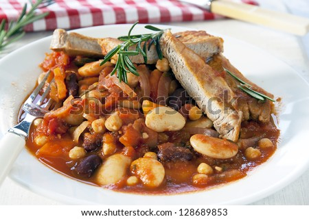 Close-up of a white plate with a meal of Boston Pork complete with beans, carrot and onions garnished with rosemary
