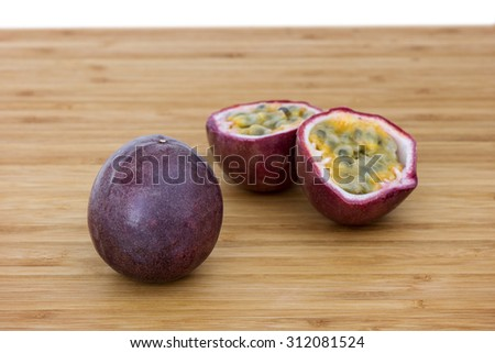Close-up of a whole and split passion fruits (passionfruit, purple granadilla (Passiflora edulis)) on a wooden table. - stock photo