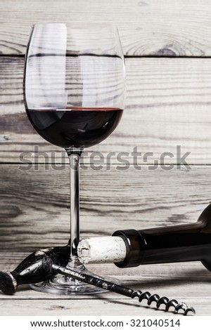 Close-up of a wine glass, a cork, a corkscrew  and a bottle on a wooden background