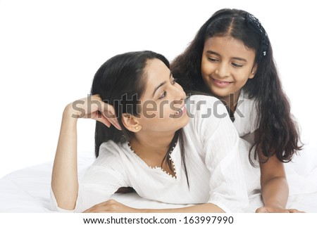 Close-up of a woman and her daughter smiling