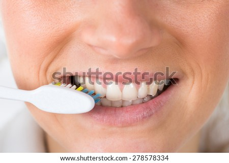 Close-up Of A Woman Brushing Teeth With Toothbrush - stock photo