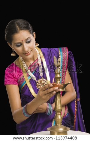 Close-up of a woman burning an oil lamp - stock photo